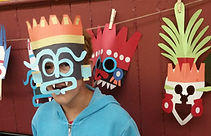 Witzilopoxtli - Un enfant portant une masque se tien devant plusieurs autre masques, A child in a mask stands in front of several other masks