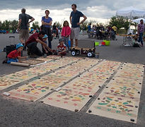 Tapis de sciure de bois coloré, Coloured Woodchip Carpets - Une groupe place les tapis dehors, A group places the carpets outside