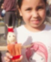 Une enfant tien sa poupée en feuille de maïs. A child hols her corn husk doll.