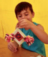 Un enfant tien sa Ojo de dios. A child holds his Ojo de Dios.