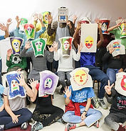 Je suis Montreal, I am Montreal - Une classe rassemble au centre du salle et tiennent leurs dessin devant leurs visages,  A class poses in he center of the room with their drawings over their faces