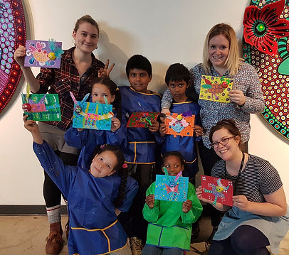 Students hold up their Alebrijs