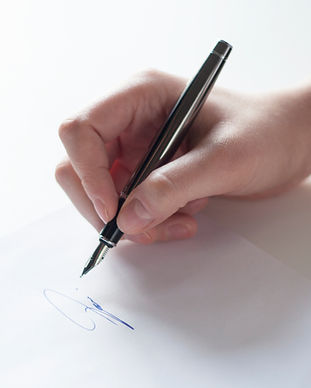 hand with pen signing a document.jpg