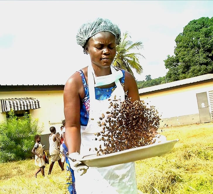 Worker checking roasted coca beans - image courtesy of The Chocolatier Ivoirien