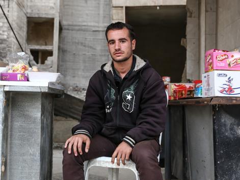 """Yassin Alghosh tue le temps en regardant le ciel depuis son stand de bonbons, coincé entre deux bâtiments déchiquetés. Lui et sa famille ont résisté aux 5 années de siège subies par leur ville: Zamalka. «Je ne suis jamais parti, mais nous vivions dans un état de terreur"""". Avec la fin de la guerre, Yassin veut retourner à l'école et finir son baccalauréat."""
