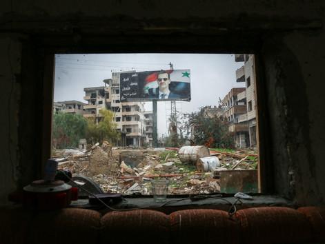 Depuis un poste de contrôle de l'armée syrienne un grand panneau de publicité avec l'image du président Bachar El-Assad règne à l'entrée de la ville de Daraya, quartier situé au sud de la capitale du pays.
