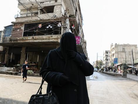 Une femme, couverte et vêtue de noir, se promène dans les rues de Kafn Batma, une petite ville de la banlieue de Damas sous le contrôle de l'armée syrienne depuis mars 2018.