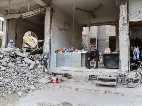 Yassin Alghosh et sa famille ont résisté pendant cinq ans au siège de leur ville : Zamalka. Après la fin des attentats, Yassin a créé un présentoir à bonbons parmi les dizaines de bâtiments détruits.