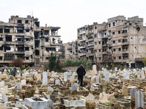 Un homme se promène parmi les pierres tombales du cimetière de Daraya, entourées par des bâtiments toujours affectés par la guerre et le siège. La ville reste inhabitée malgré le contrôle de l'État depuis 2016. On observe seulement un groupe d'une demi-douzaine d'hommes assistant à des funérailles dans le cimetière de la ville, où reposent un bon nombre de ceux qui ont péri lors des bombardements.