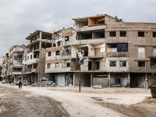 Une grande affiche représentant le président syrien Bachar El-Assad domine le centre d'une rue transversale de la ville de Zamalka, une ville située à dix kilomètres de Damas, qui, après sa libération, tente de revenir à la normale.