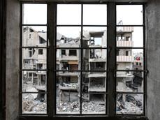 Vue de l'un des quartiers du centre de Harasta, ville sous le contrôle de l'armée syrienne depuis mai 2018, à travers une fenêtre sans vitre d'un bâtiment également touché par la guerre.