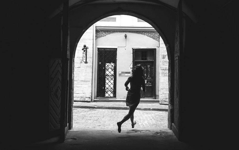Woman running through arch onto cobbled street