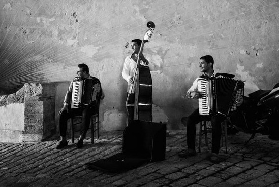 Black and white shot of two accordion players and a double bass player on a cobbled street