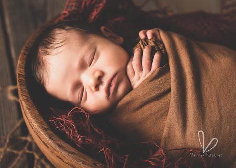 Nouveau-né dort dans le panier avec noix dans les mains.