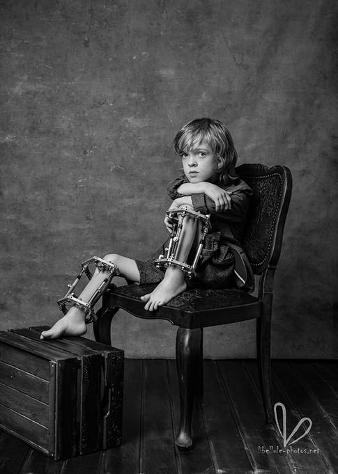 Garçon sur une chaise. Photo monochrome. Studio Libellule-photos à Molsheim.