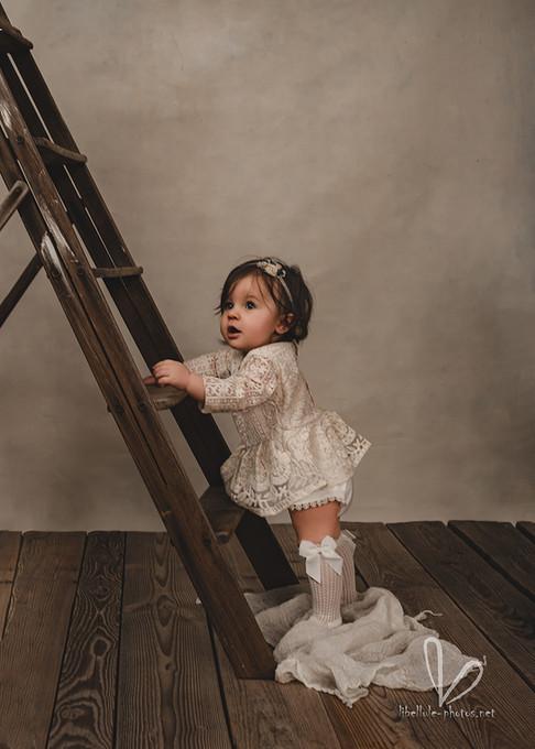 Belle petite fille à coté d'une echelle.