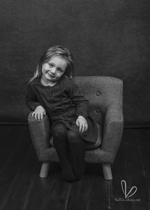 Jolie fille sur une chaise. Noir et blanc. Séance photos en studio Libellule-photos.