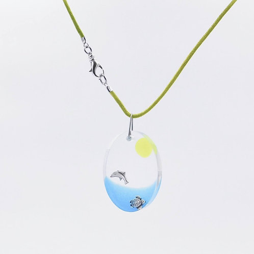 Handmade sea inspired dolphin and sea turtle playing in a resin surf necklace.