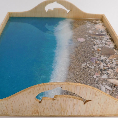 Side view of handmade sea inspired wood and resin beach serving tray with dolphin handles, and sand, shells, and shark teeth.