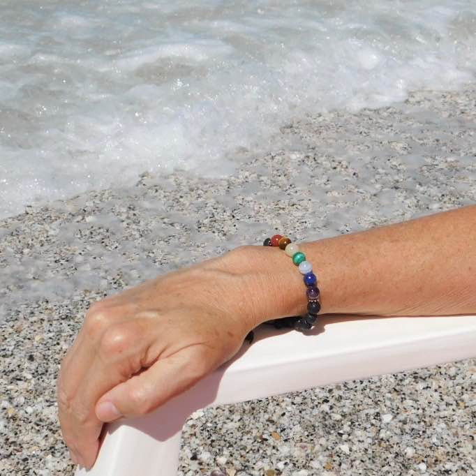 Woman wearing handmade Chakra bracelet at the beach.