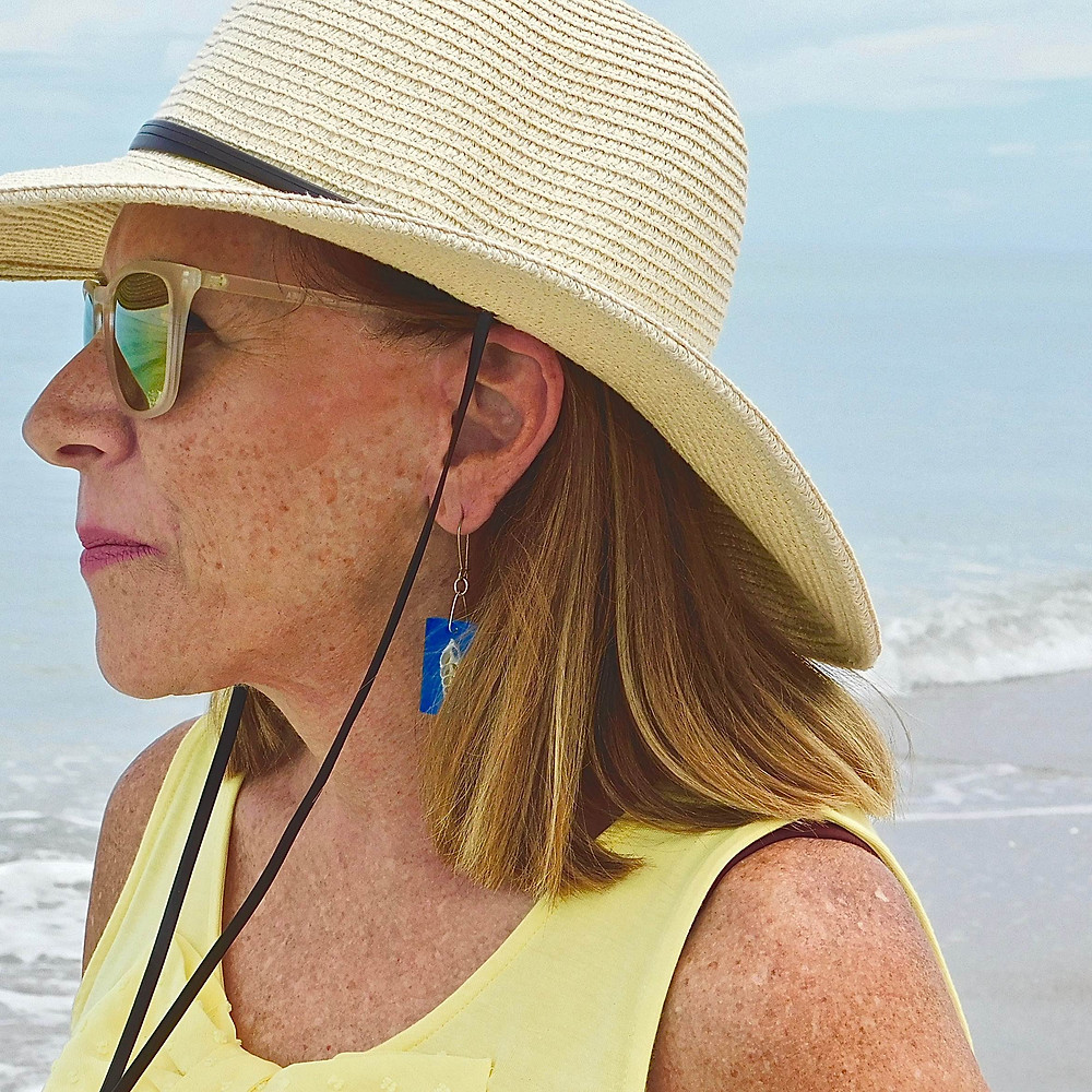 Woman wearing hat, sunglasses, real shell earrings, at the beach.