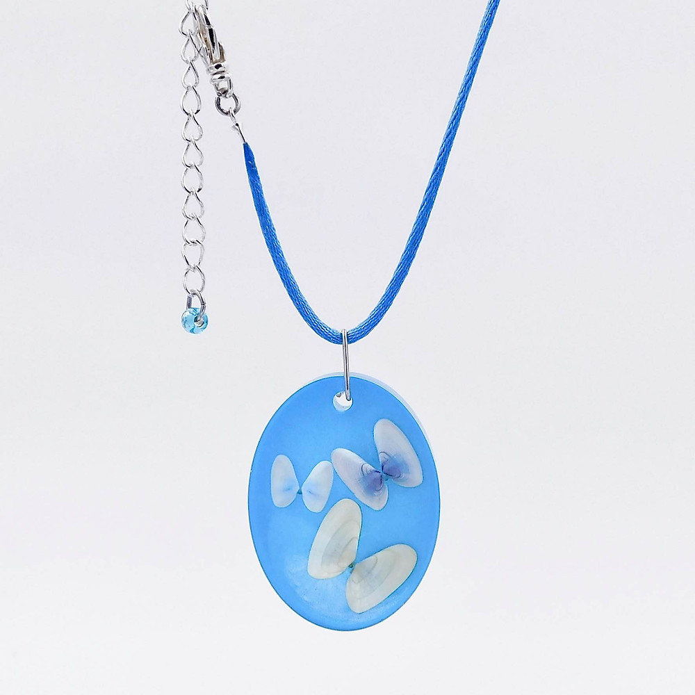 Multiple-coquina-shells-in-light-blue-resin-necklace.