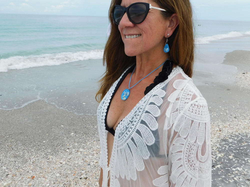 Handmade coquina shell jewelry worn by a woman at the beach.