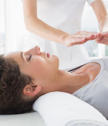 A woman receving a Reiki treatment