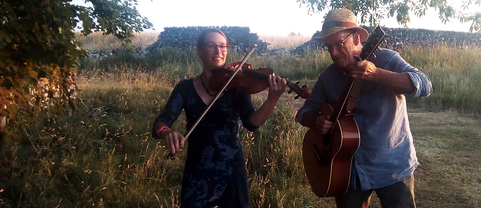 Jen and Jon from The Moonbeams, with their viola and guitar standing by a rocky beck. There is a grassy bank behind them and then a field, wall and tree further in the distance