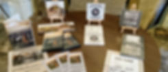A round table with The Moonbeam Collective merchandise. Sparrowhawk's Eye, Watching Wildlife and This Land albums are on display on mini easels. There are also Streams of Wonder DVDs and flyers.