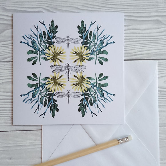 Greeting card with watercolour flowers and leaves and dragonflies with a white envelope