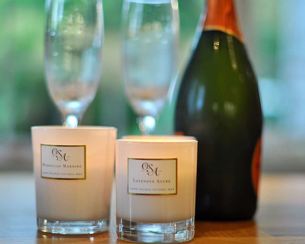 Two candles burning in the foreground with a champagne bottle in the background