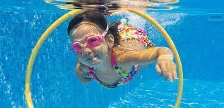 child swimming through hoop
