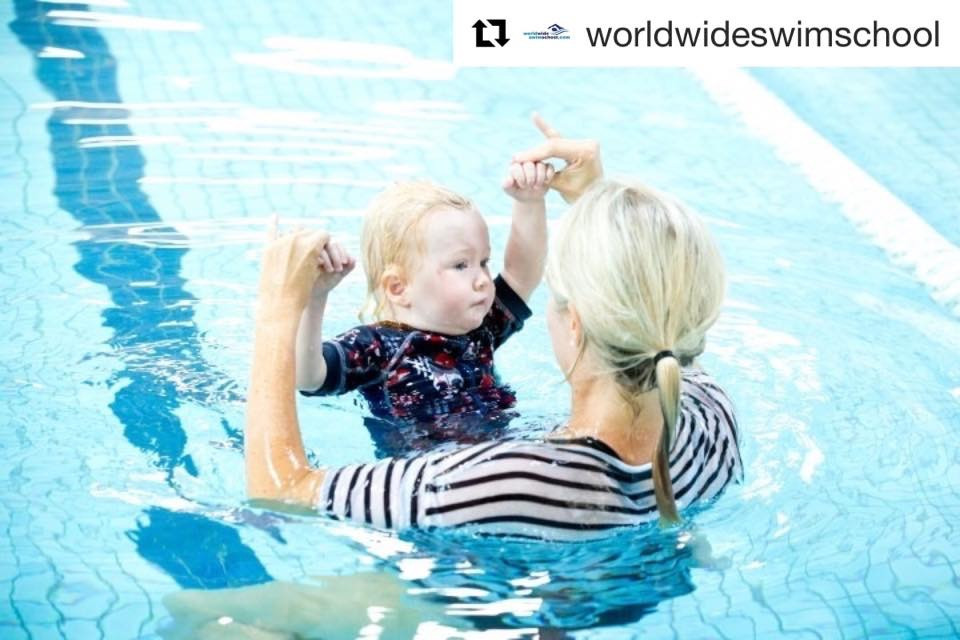 baby grasping adult fingers in water