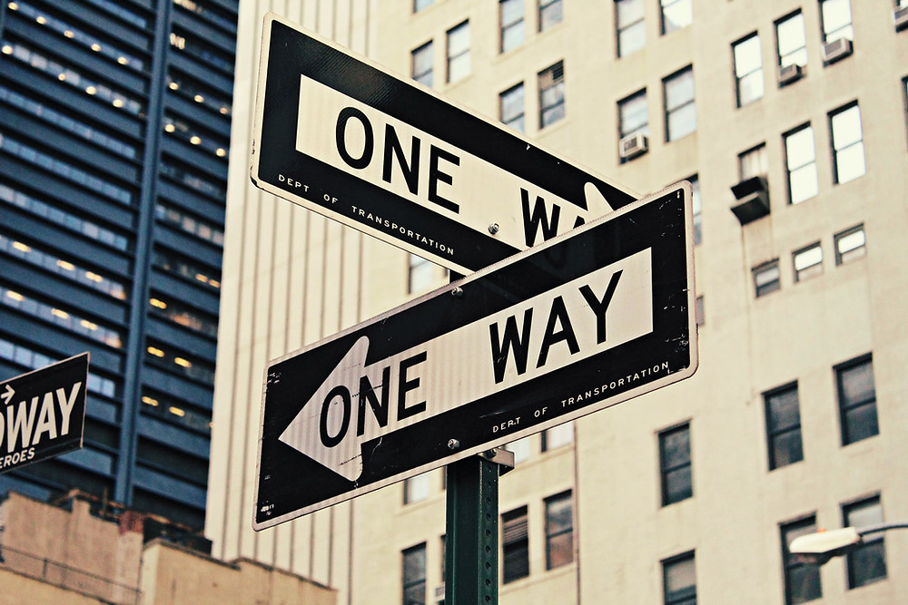 Two one way signs on a street symbolising the difference between emotional and rational Facebook app marketing strategies..