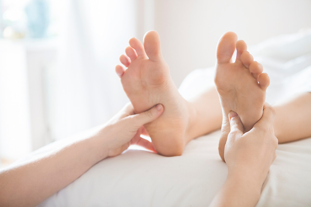 Therapist holding the feet in foot reflexology
