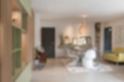 Ondine Rebillard Architecte d'intérieur et décoratrice à Lyon - le claustra déjà présent dans l'entrée, réalisé dans un boisde la même teinte que la cuisine, aservi de référence et point de départ au projet. Nous avons choisi de mêlercette teinte bois à un vert kaki également très naturel et très doux rappelantl'immense écrin de verdure auquel le salon fait face.Le jeu des pleins et des vides, les panneaux coulissants et l'apport d'un éclairageadapté permettent de moduler à volonté la décoration. Un meuble télévisionet une console complètent ce décor entièrement réalisé sur mesure en s'y intégrant en toute harmonie.