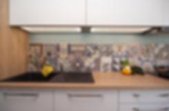 Une verrière a été imaginée sur la cloison qui sépare la cuisine du salon/séjour, mais aussi en retour sur le mur du couloir afin de lui faire bénéficier d'un maximum de luminosité. Une porte coulissante permet à mes clients de pouvoir isoler phoniquement la cuisine du salon quand ils en ont le besoin. La cuisine a elle été traitée dans des teintes douces mais avec des touches plus vives notamment grâce à la faïence. Mes clients ont gagné un coin repas confortable, des rangements, et de la clarté! Ondine Rebillard Architecte d'intérieur à Lyon