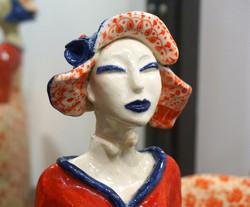 femme au chapeau bleu levre bleu fleur rouge