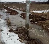 Бурные потоки воды вдоль дороги от магазина