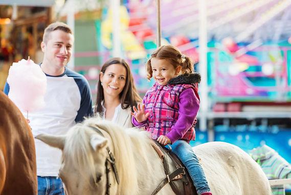 Girl enjoying pony ride, fun fair, paren
