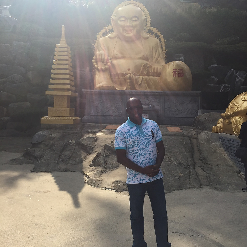 Béché Emmanuel devant une statue de Bouddah