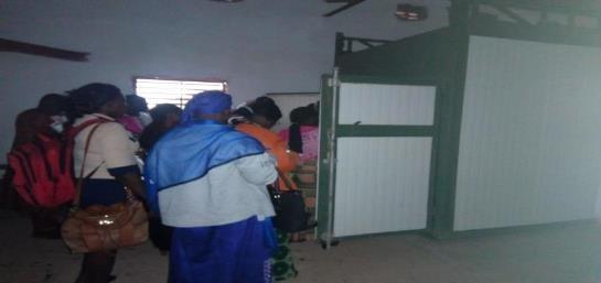 Les participant.e.s visitant l'intérieur du séchoir tunnel de la coopérative PAOLINE