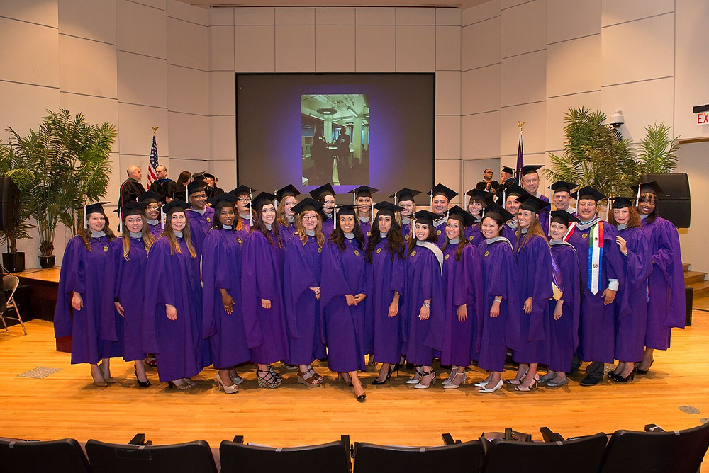A group of people in graduation caps and purple gowns on stage.