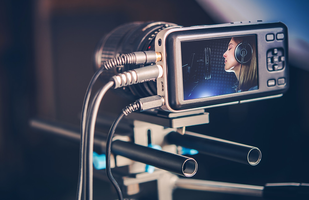 camera recording woman singing for video streaming