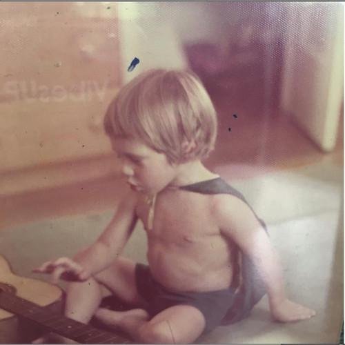 Jason age 2 with his first guitar in batman cape. Berkeley California