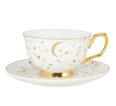 tea cup and saucer with stars and moon pattern in gold