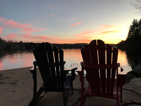 two_empty_adirondack_chairs_near_body_of
