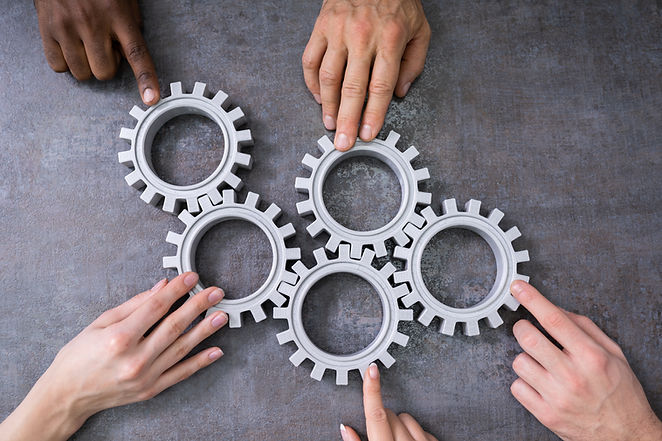 Group Of Businesspeople Joining Together Gears On Table At Workplace.jpg