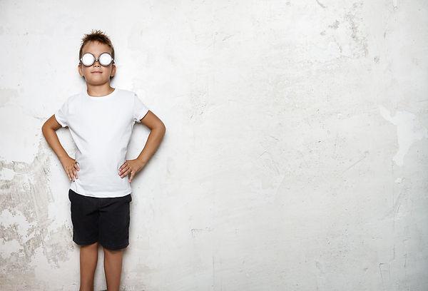 Boy wearing white tshirt, shorts stands